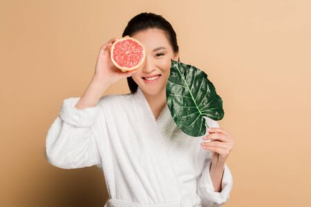 happy beautiful asian woman in bathrobe with grapefruit half and leaf on beige background