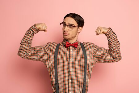 thoughtful male nerd in eyeglasses showing muscles on pink
