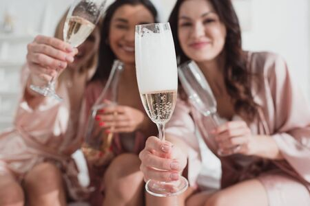 Selective focus of happy multiethnic friends holding champagne glasses and looking at camera at bachelorette party Stockfoto