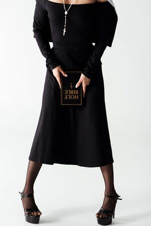 cropped view of nun in black dress holding bible on grey