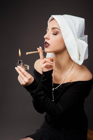 attractive nun smoking marijuana joint with lighter on grey Stock Photo