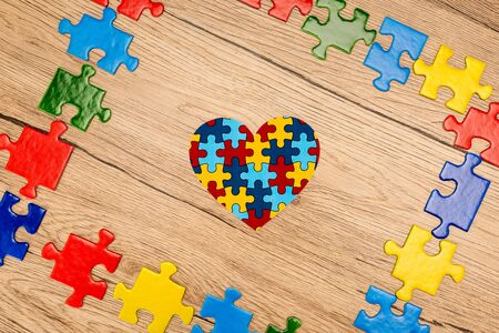 Top view of puzzle heart on wooden background, autism concept