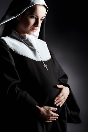 crying pregnant nun touching tummy on grey