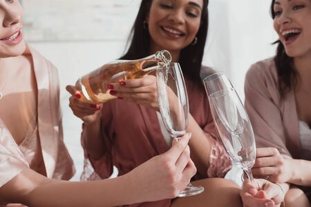 Partial view of african american girl pouring champagne in glasses with friends at bachelorette party
