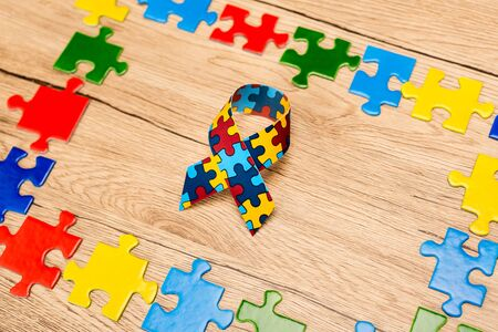 High angle view of awareness ribbon with pieces of puzzle on wooden background, autism concept