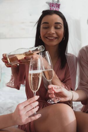Cropped view of african american bride pouring champagne in glasses with friends at bachelorette party