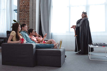 KYIV, UKRAINE - JANUARY 27, 2020: handsome man in fairy king costume talking to attentive friends sitting on sofa