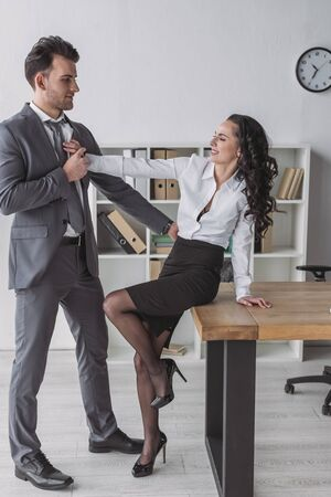 smiling secretary sitting on desk and pushing away businessman molesting her in office