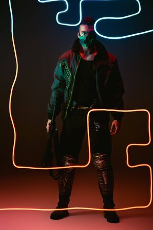 mixed race cyberpunk player in protective mask holding gun while standing near neon lighting on black