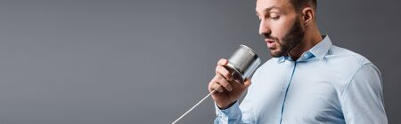 panoramic shot of bearded man taking while holding tin can isolated on grey