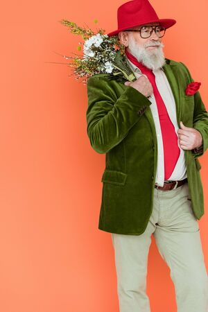 Stylish senior man posing with bouquet of wildflowers isolated on coral
