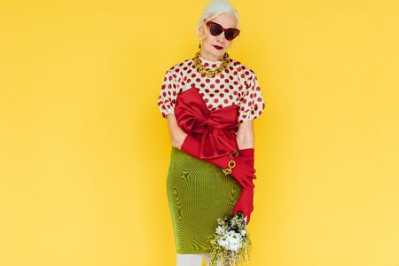 Beautiful elderly woman in sunglasses holding bouquet of wildflowers isolated on yellow