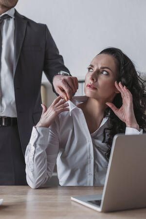 cropped view of businessman touching blouse of angry secretary sitting at workplace 版權商用圖片