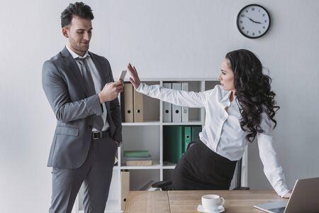displeased secretary showing stop gesture at businessman taking her photo on smartphone 版權商用圖片