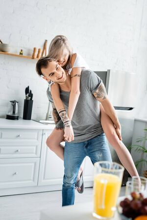 Selective focus of girl piggybacking on tattooed boyfriend near fruits and orange juice on kitchen table