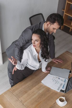 high angle view of businessman touching buttocks of angry secretary standing at workplace