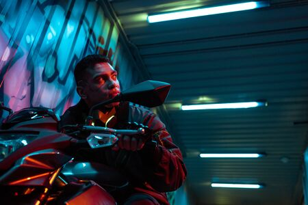 low angle view of mixed race cyberpunk player on motorcycle