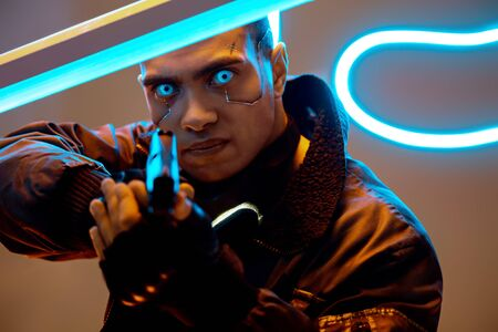 selective focus of handsome and mixed race cyberpunk player with metallic plates on face and blue eyes holding gun near neon lighting Фото со стока