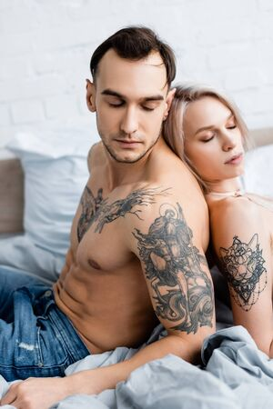 Side view of handsome tattooed man sitting back to back with attractive girl on bed