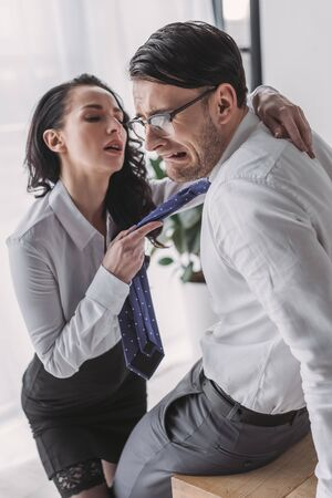 sexy secretary holding tie and hugging scared boyfriend while seducing him in office