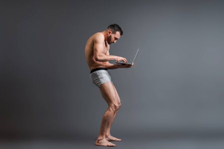 bearded and stooped man in boxer shorts using laptop on grey