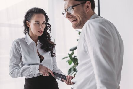 businessman seducing colleague in office while touching his belt
