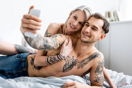 Selective focus of smiling tattooed couple taking selfie with smartphone on bed