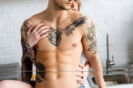 Cropped view of woman touching torso of muscular tattooed boyfriend in kitchen