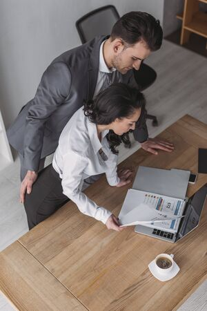 high angle view of businessman touching buttocks of secretary looking at papers