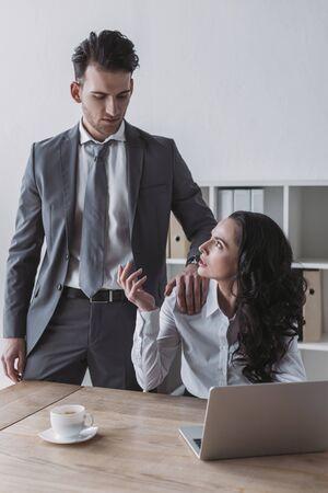 displeased secretary looking at businessman touching her shoulder 版權商用圖片