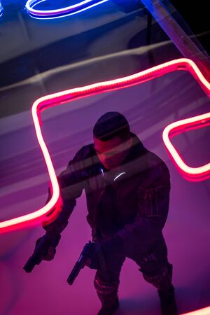 overhead view of armed mixed race cyberpunk player holding guns near red neon lighting Фото со стока