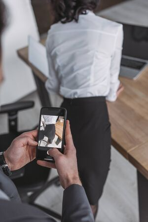 cropped view of businessman taking photo of buttocks of secretary on smartphone 版權商用圖片