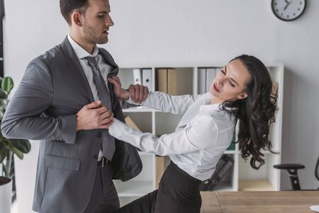 displeased secretary pushing away businessman molesting her in office 版權商用圖片