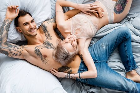 Top view of tattooed man smiling at camera near girlfriend in lingerie on bed