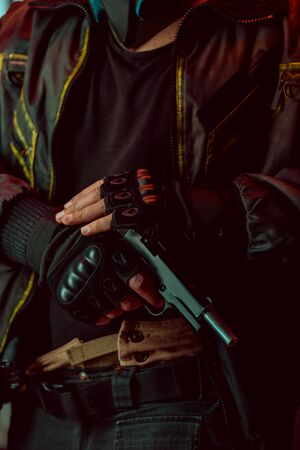 cropped view of armed cyberpunk player in gloves holding gun
