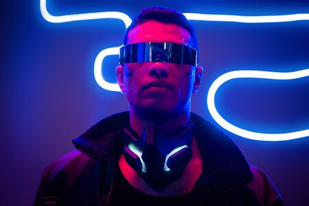 mixed race cyberpunk player in futuristic glasses near blue neon lighting