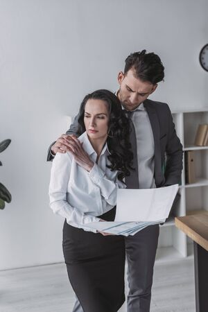 handsome businessman touching shoulder of attractive secretary holding papers
