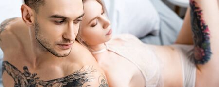 Panoramic shot of muscular tattooed man sitting on bed near sexy girlfriend in lingerie 版權商用圖片