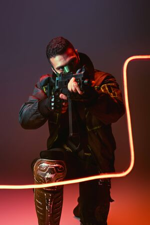 bi-racial cyberpunk man in mask aiming gun near neon lighting on black Banque d'images