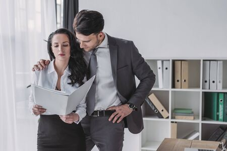 handsome businessman touching shoulder of beautiful secretary holding papers 版權商用圖片