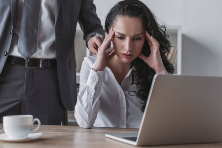 cropped view of businessman touching shoulder of tired secretary sitting at laptop