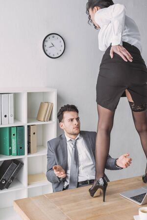 Schockierter Geschäftsmann, der die Sekretärin in hochhackigen Schuhen auf dem Schreibtisch anschaut