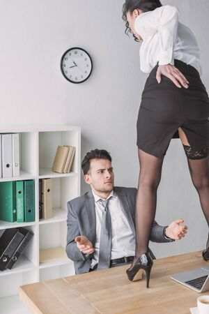 shocked businessman looking at sexy secretary standing on desk in high heeled shoes Stock Photo