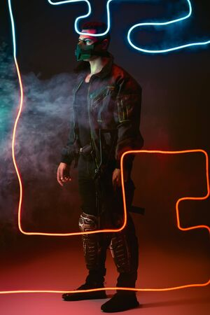 armed mixed race cyberpunk player in protective mask standing near neon lighting on black with smoke