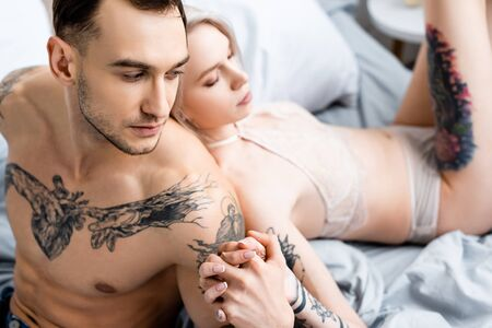 Selective focus of tattooed man holding hand of sensual woman in lingerie on bed