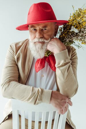Handsome senior man in red hat holding wildflowers and looking at camera on chair isolated on white 版權商用圖片