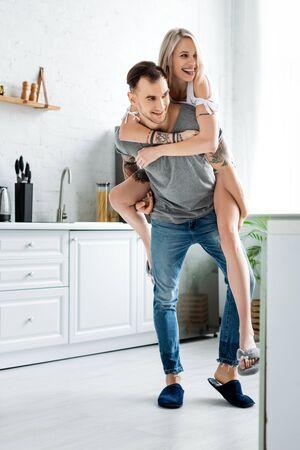 Smiling girl piggybacking on back of tattooed boyfriend in kitchen