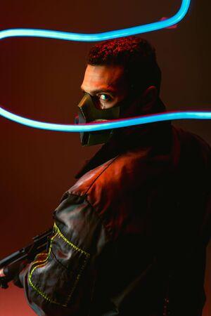 selective focus of bi-racial cyberpunk player in protective mask holding gun near blue neon lighting on black