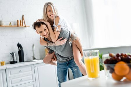 Selective focus of smiling girl piggybacking on tattooed boyfriend near fruits and orange juice on kitchen table
