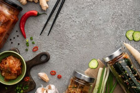 top view of tasty kimchi in jars and bowl near chopsticks, green onions, ginger, garlic and chili pepper on concrete surface